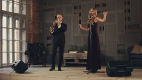 Jazz vocalist in dark dress and saxophonist in suit perform on stage. Duet. stock footage