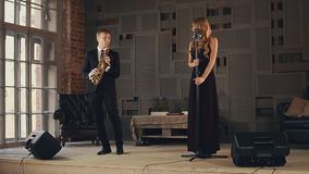 Jazz vocalist in dark dress and saxophonist in suit perform on stage. Smile. stock footage