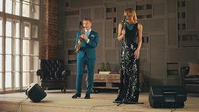 Jazz vocalist in dress and saxophonist in blue suit perform on stage. Elegance stock video