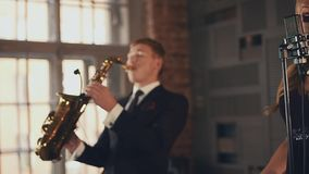 Jazz vocalist in dress and saxophonist in suit perform on stage. Retro style stock video