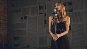 Jazz vocalist in elegant dress perform on stage at microphone. Dark pomade. Jazz vocalist in elegant dress perform on stage at microphone. Dark pomade on lips stock video footage