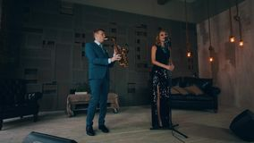 Jazz vocalist in glowing black dress performing on stage with saxophonist. Retro style stock footage
