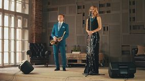 Jazz vocalist in glowing dress and saxophonist in blue suit stand on stage. Retro style. Duet stock video