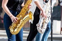 Jazzband von jungen Musikern mit den Saxophonen, die während m durchführen stockbilder