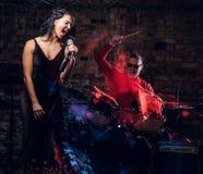 Jazzbandkapacitet Koppla ihop av musiker - en handelsresande och en sångare i en nattklubb royaltyfri fotografi