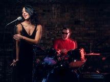 Jazzbandkapacitet Koppla ihop av musiker - en handelsresande och en sångare i en nattklubb royaltyfria bilder