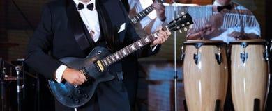 Jazzbandkapacitet Närbild En abstrakt man i en strikt dräkt spelar gitarren på scenen i förgrunden Valsar i arkivfoto