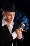 Jazzman and retro microphone. In suit and hat stock photo