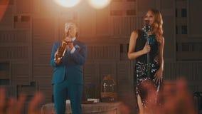 Jazzsänger im Tanz des grellen Glanzes Kleiderführen mit Saxophonisten im blauen Anzug durch stufe stock video