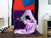 Jazzstillleben mit einem Zylinder und einem Saxophon auf purpurrotem Stoff stockfoto