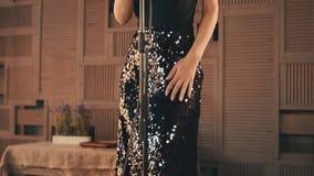 Jazzvokalisten, i att bedöva klänningen, utför på etapp elegantt Mikrofon dans arkivfilmer