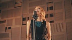 Jazzvokalisten i glödande klänning utför på etapp elegantt dans Man upp arkivfilmer