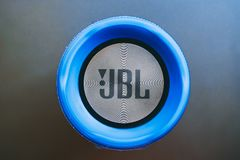 JBL Charge 3. Bishkek, Kyrgyzstan - February 24, 2018: JBL logo on a blue bluetooth speaker with textile and metalic texture. Flat lay stock photography