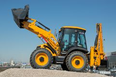 The JCB backhoe loader stands on the advertising stand in the south of the city. Inscription on a tractor - made in Russia SAINT- royalty free stock photo