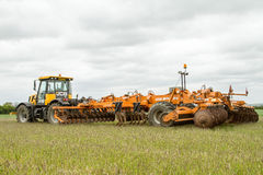 JCB fastrac tractor with cultipress simba solo 600. A orange simba cultipress solo 600 plough roller and roll rings farming machinery pulled by a jcb fastrac Stock Photos
