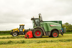 A JCB fastrac tractor with Fendt Katana 65 forager. A JCB 3170 fastrac tractor with Fendt Katana 65 forager harvester harvesting silage and bailey trailer Royalty Free Stock Images