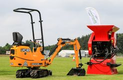 Jcb mini digger and red rhino mini crusher. Jcb mini excavator c8008 and red rhino stone crusher for landscaping and excavating at country show royalty free stock image