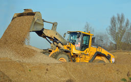 JCB working in gravel yard. Royalty Free Stock Image