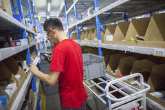 JD.com staff receiving incoming goods. Gu'an, China - June 14, 2016: JD.com staff receiving incoming goods, sorting products, and preparing shipments at the Stock Photos