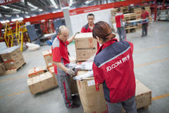 JD.com staff sorting packages. Gu'an, China - June 14, 2016: JD.com staff receiving incoming goods, sorting products, and preparing shipments at the Northeast Stock Photos