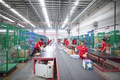 JD.com staff sorting packages. Gu'an, China - June 14, 2016: JD.com staff receiving incoming goods, sorting products, and preparing shipments at the Northeast stock photo
