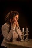 Jüdische Frau betet über Sabbat-Kerzen Stockfotos