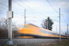 Jeûnent le train jaune sur l'image brouillée ferroviaire de mouvement Photographie stock