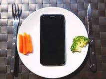 Jeść mądrze telefon na naczyniu fotografia stock