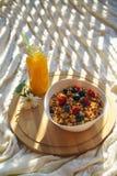 Jeść zdrowego śniadaniowego granola świeże jagody w białym pucharze i świeżym pomarańczowym juce na round drewnianym biurku na wy fotografia royalty free