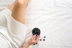 jeść zdrowo pojęcia Kobieta ma czarne jagody w łóżku Zdjęcia Stock