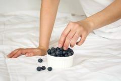 jeść zdrowo pojęcia Kobieta ma czarne jagody w łóżku Obraz Royalty Free