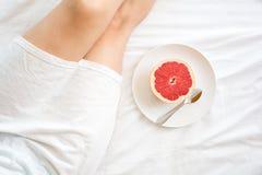 jeść zdrowo pojęcia Kobieta ma grapefruitowego w łóżku Obraz Stock