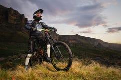 Jeździec w pełnej ochronie na roweru górskiego spojrzeniach przy zmierzchem na tle skały i stojakach Obrazy Royalty Free