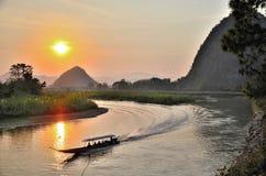 Jeździecka łódź wzdłuż rzeki gdy słońce set Obrazy Royalty Free