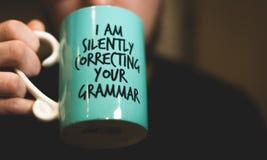 Je corrigeant secrètement votre tasse de café de grammaire image stock