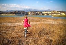 Jeździecki rower w polu w kierunku jeziora Fotografia Royalty Free