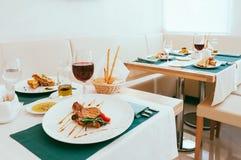 Je lunch jedzenie s?uzy? w restauracji, ?licznym ustawianiu z posi?kiem i win szk?ach, fotografia stock