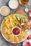 je lunch z kurczak bryłkami, francuskimi dłoniakami, świeżą sałatką i piwem, fotografia stock