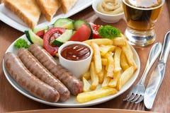 Je lunch z piec na grillu kiełbasami, Francuskimi dłoniakami, warzywami i piwem, fotografia royalty free