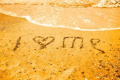 Je m'aime écrit sur le sable d'une plage Photographie stock