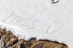 Je manque U écrit dans la neige Image stock