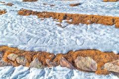 Je manque U écrit dans la neige Image libre de droits