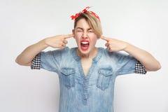 Je ne veux pas à ici Portrait de crier la jeune femme mécontente dans la chemise bleue de denim et le bandeau rouge se tenant et  photo libre de droits