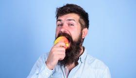 Je nutrition de régime d'homme de pommes d'amour mange du fruit Concept sain de nutrition Hippie beau d'homme avec la longue cons Photographie stock libre de droits
