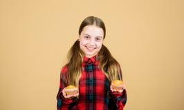 Je peux manger des gâteaux toute la journée Sourire heureux de petit enfant avec des g?teaux de tasse Petite fille heureuse tenan photo libre de droits