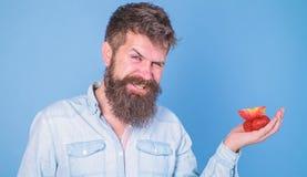 Je prends des festins pour vous L'homme offre d'essayer des fraises et le fruit de pomme traite le fond bleu Prises barbues de hi image stock