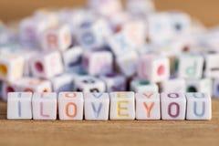 Je t'aime écrit dans la lettre perle sur le fond en bois Image stock