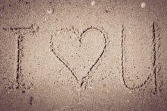 Je t'aime écrit sur le sable Photos stock