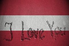 Je t'aime écrit sur le sable avec mélanger le drapeau de l'Autriche Photo libre de droits