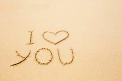 Je t'aime écrit sur le sable jaune humide de plage Photos libres de droits